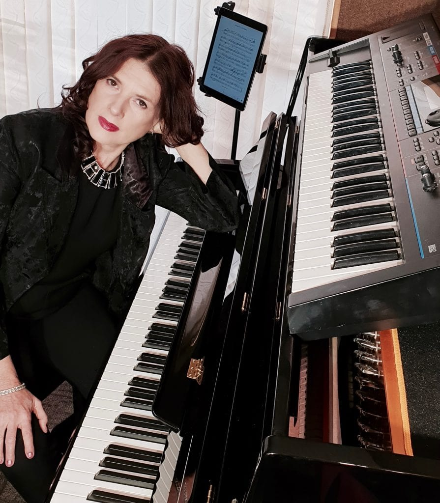 Linda McGann pianist at her keyboard and piano